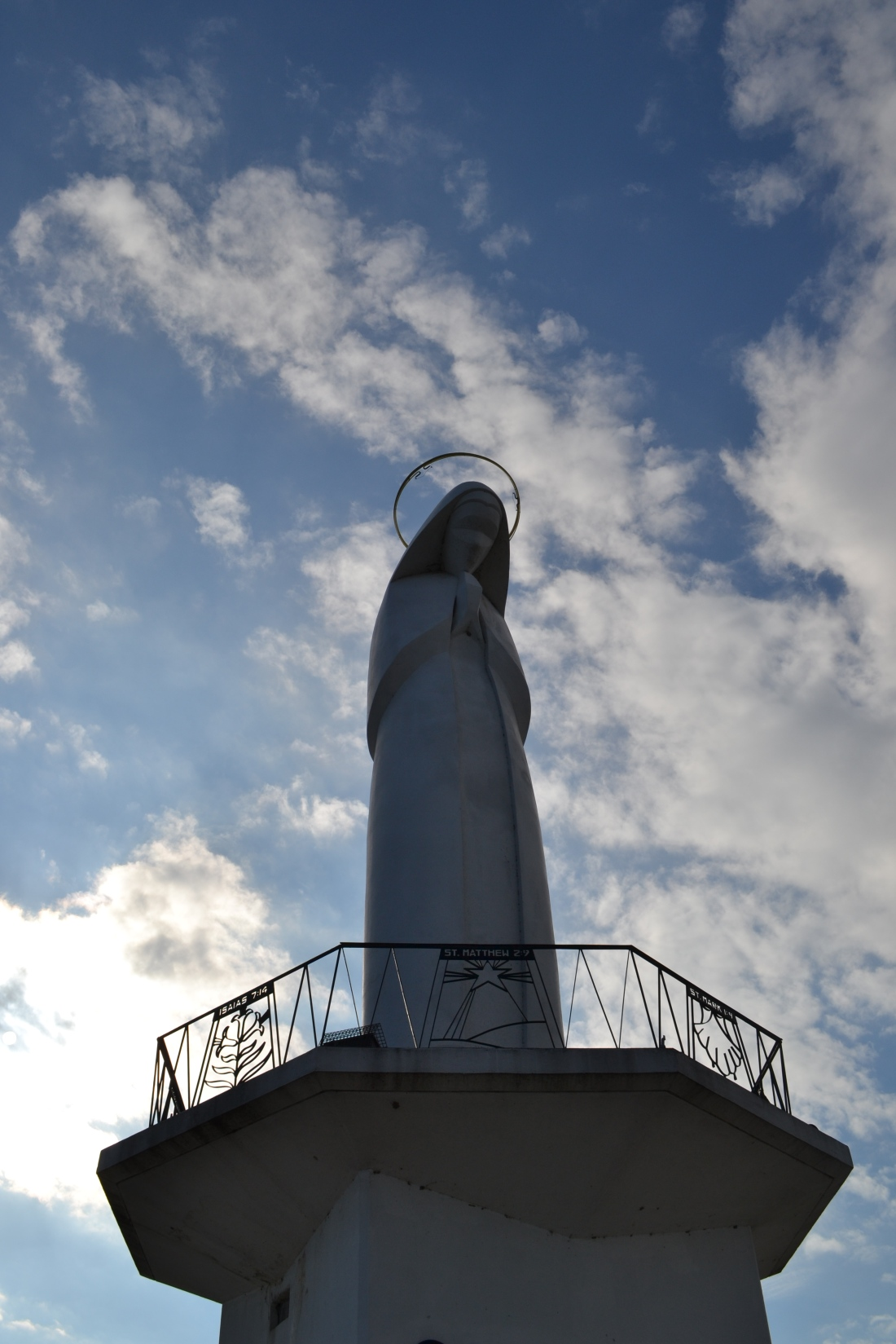 A statue of the Virgin Mary, her head bowed and hands reposed in prayer. The statue faces the riverfront in the township of Portage de Sioux, MO.