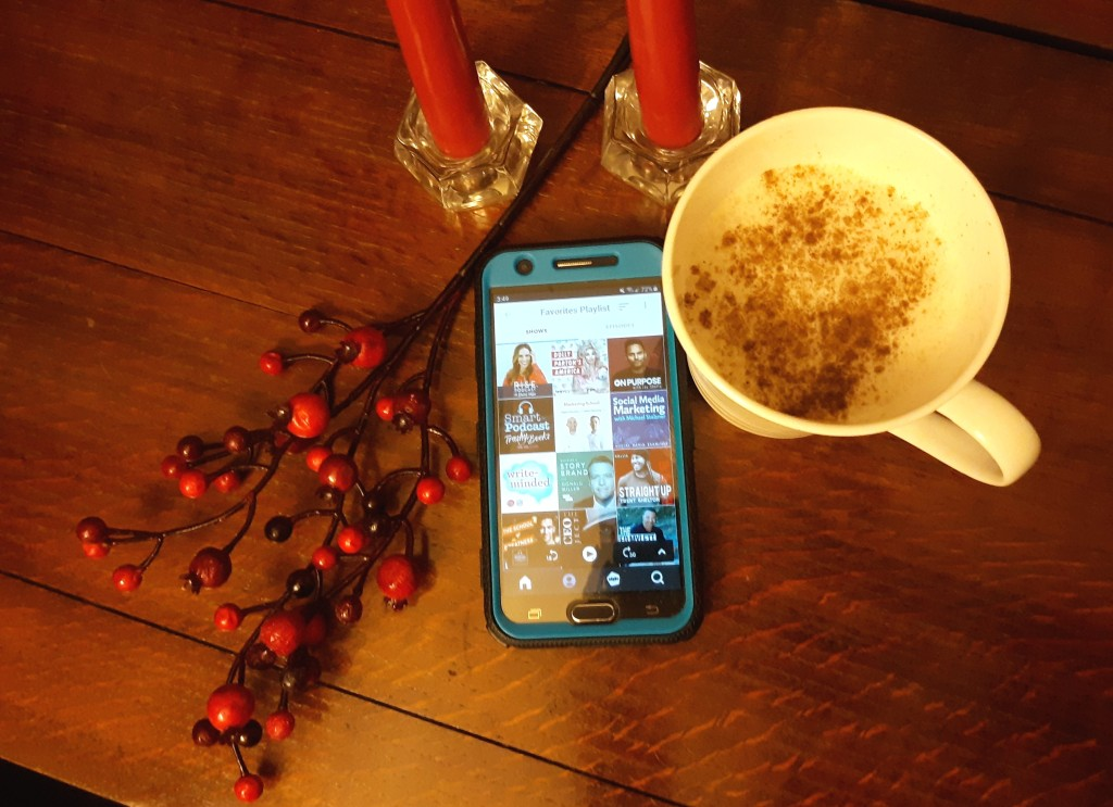 A cup of eggnog, a cellphone with a podcast app open, red candles on a table.
