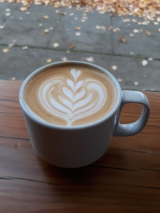 A latte in a coffeeshop window with fall leaves